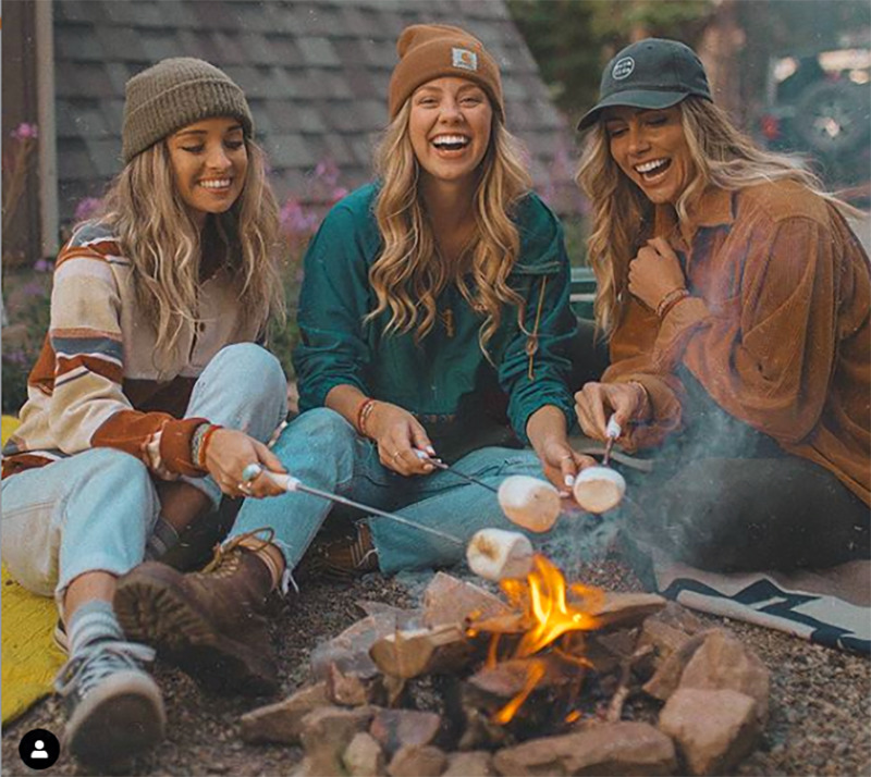 Three girls smile and laugh while roasting marshmellows around a small fire