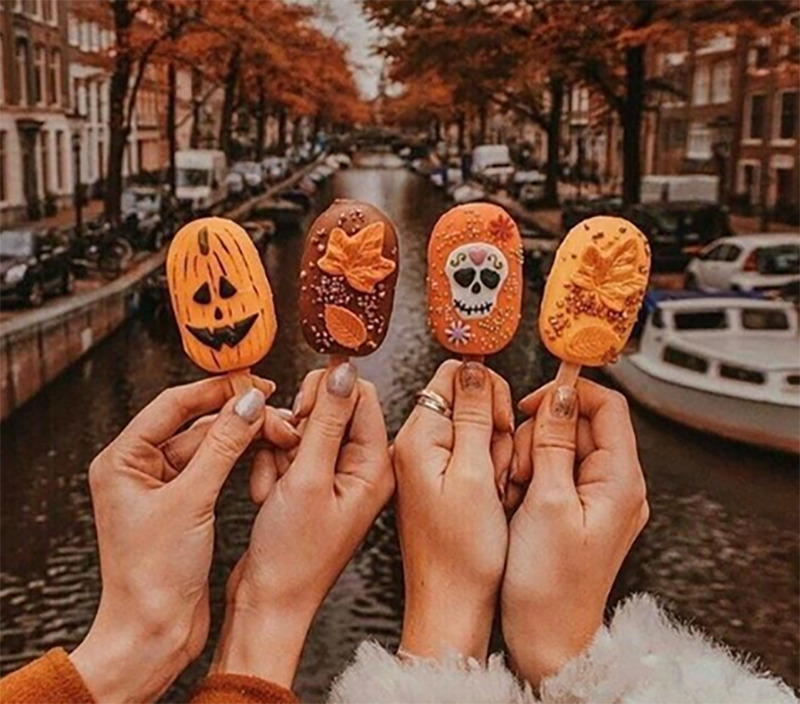 Girls hold autumn-inspired cake pops up in front of a street lines with autumn trees