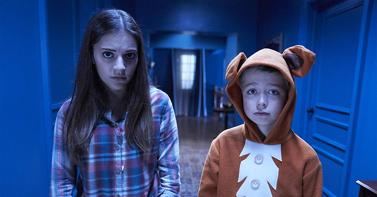 a teenage girl and a young boy in a costume standing in a hallway