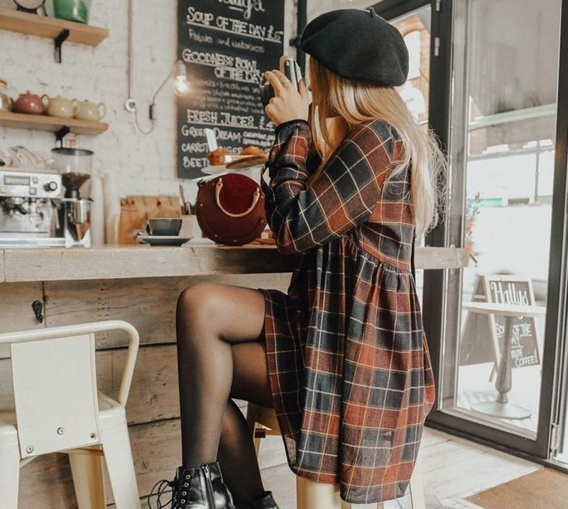 A girl looks through a camera while sitting at the counter in a coffee shop