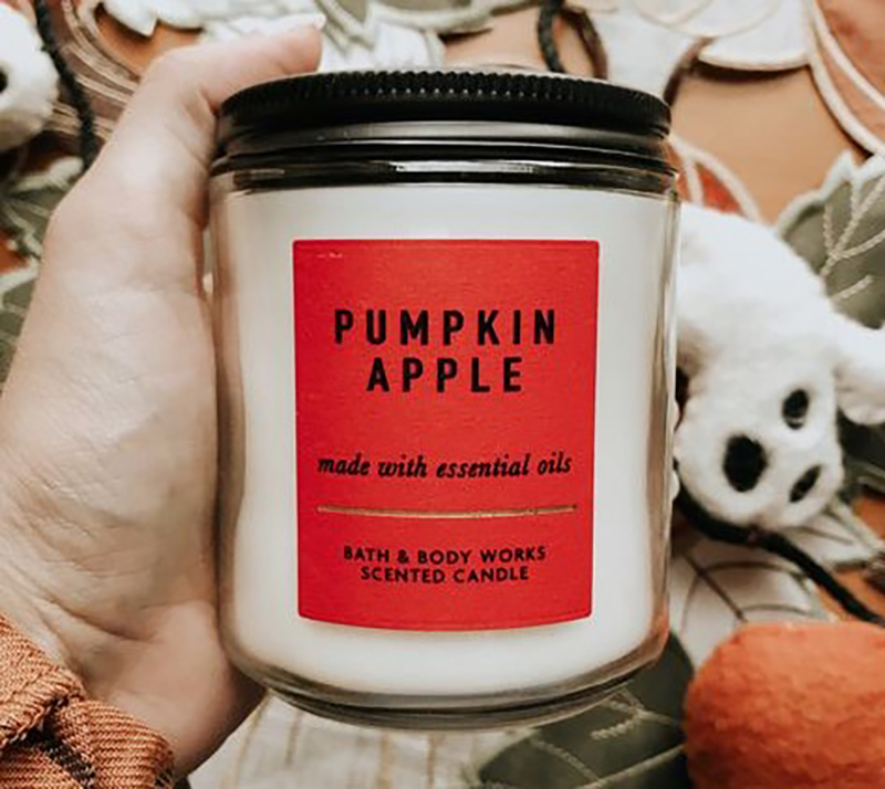 A woman shows off her Pumpkin Apple scented candle