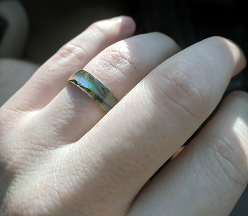 A woman wears a mood ring on her wedding finger