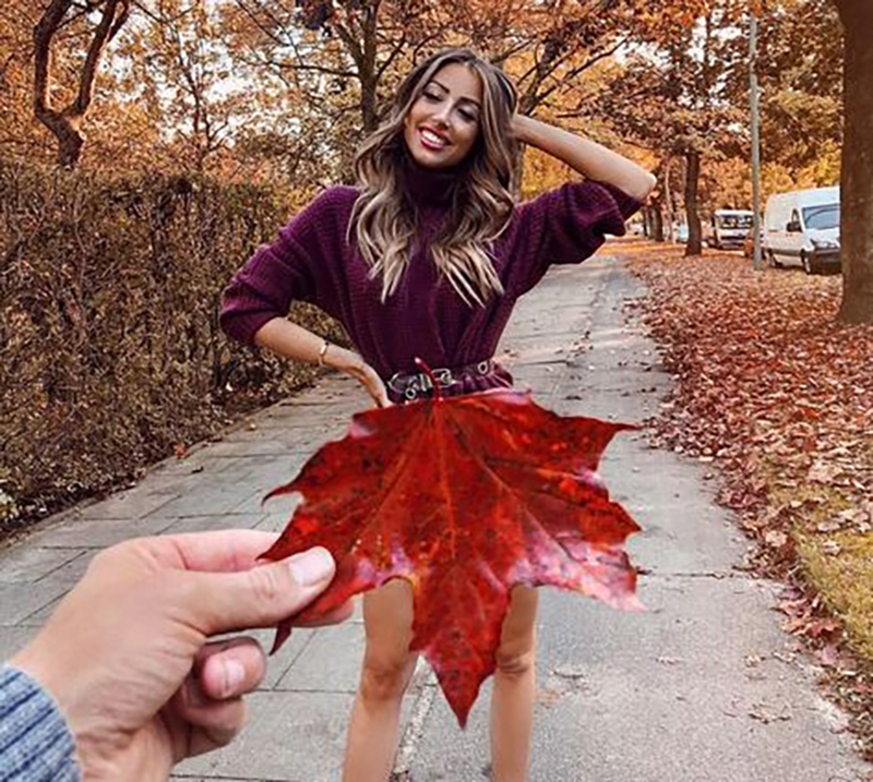 The photographer holds up an upside down leaf in front of the model so that is appears that she's wearing the leaf as a skirt