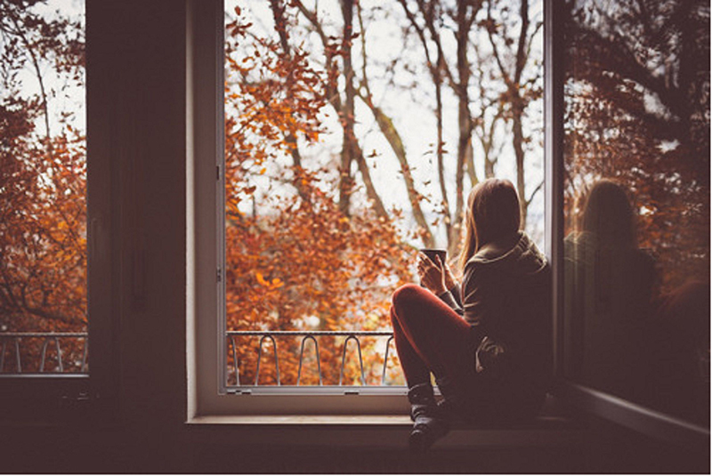 A girl is photographed from behind sitting on a window sill before fall trees
