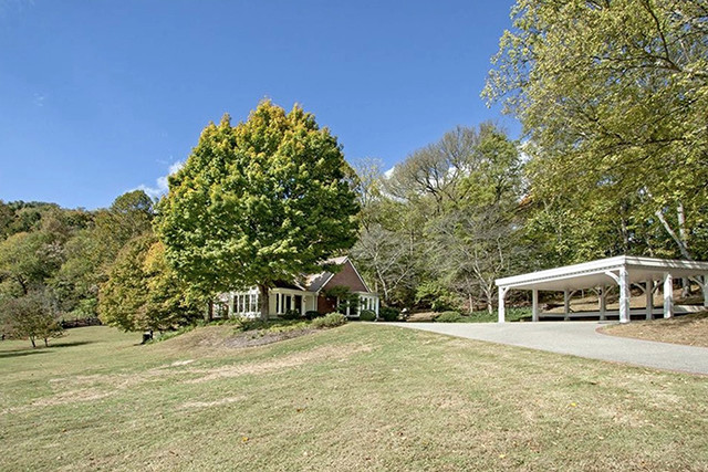 A picture of the estate from a distance shows grass, trees, a large carport, and a long driveway