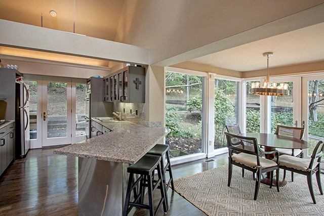 A long kitchen looks on to a breakfast nook surrounded by glass windows.
