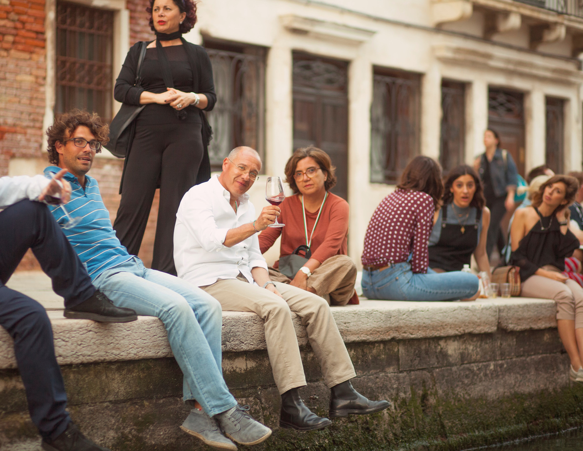 Tourists enjoy wine while sitting along a canal in Venice, Italy
