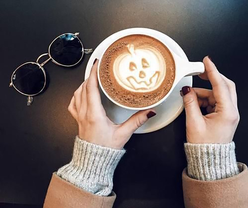 An image from above shows a pumpkin latte gripped by two female hands