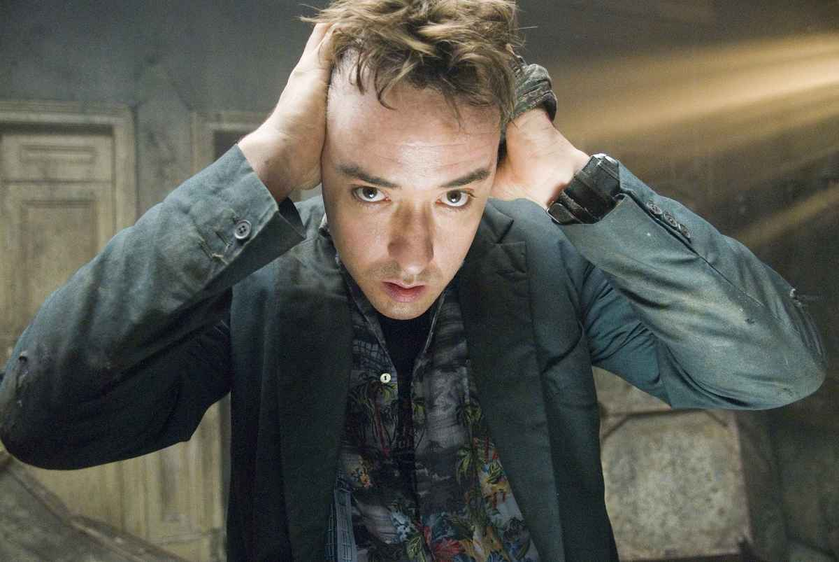 John Cusack holds his hands to his ears while standing in a disheveled room