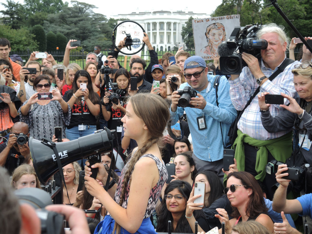 Greta speaks through a megaphone at a crowd of ralliers in front of the White House