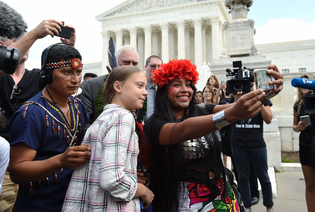 A woman takes a selfie with Greta in front of the Supreme Court building