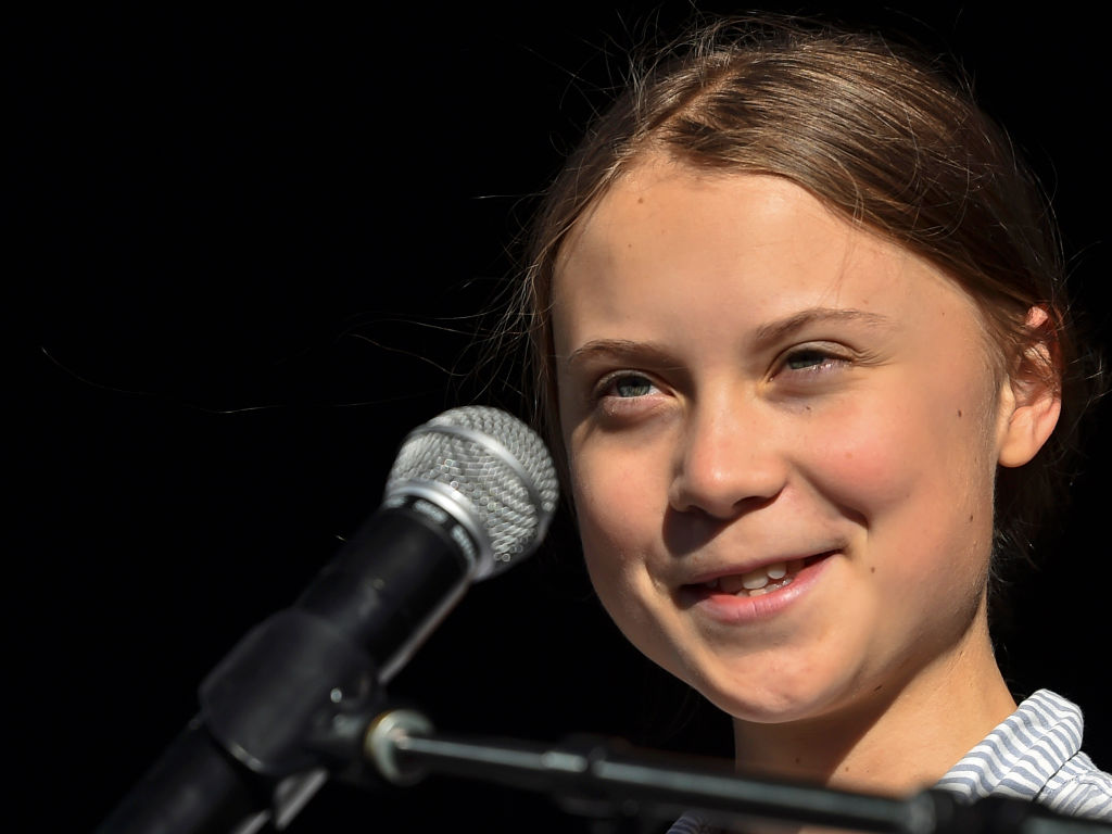 Greta grins in front of her microphne onstage