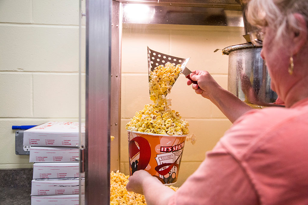 Woman filling up popcorn bucket