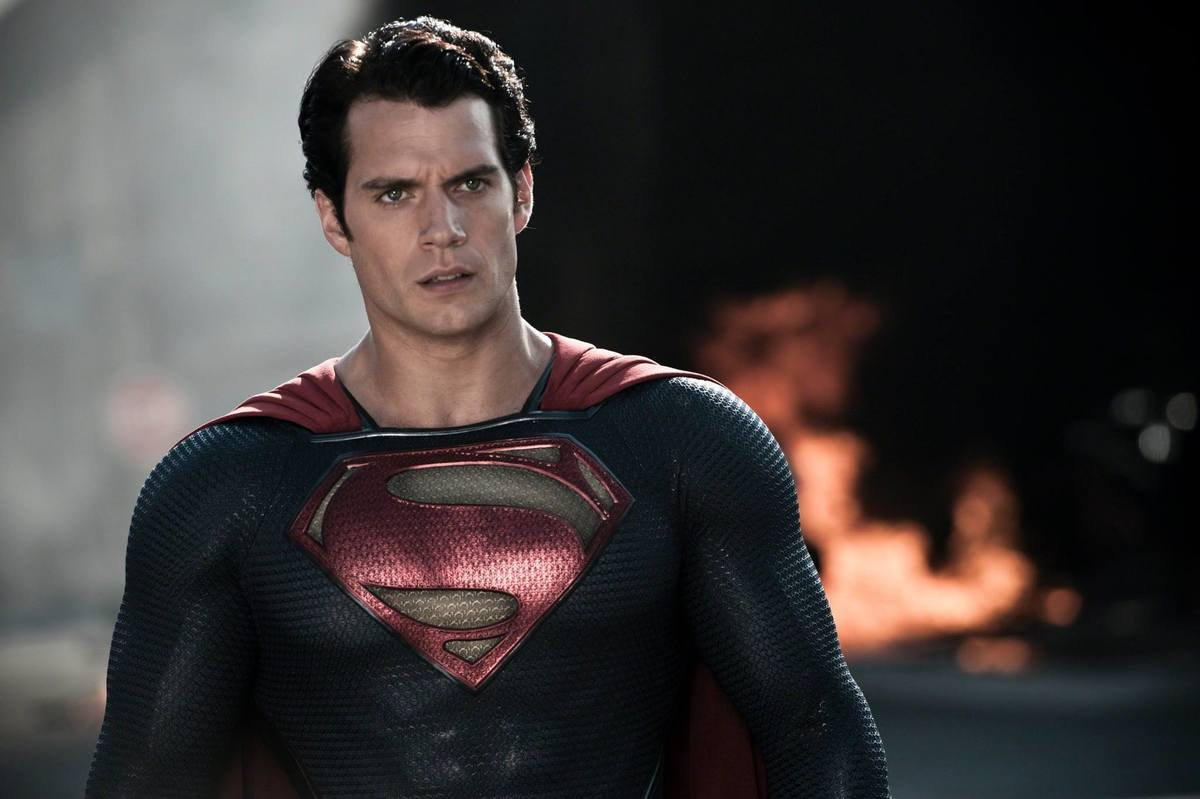 Superman looks serious while walking from a fire