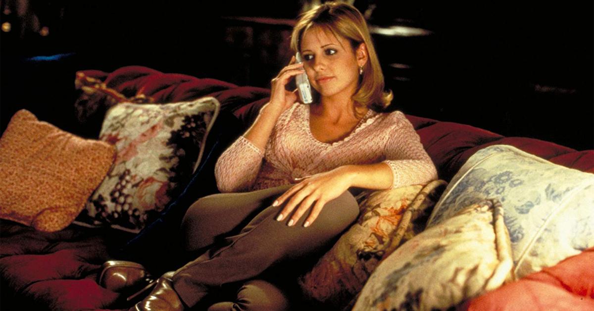 sarah michelle gellar sitting on a couch talking on a landline phone