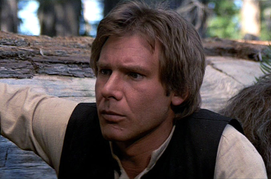 Han Solo crouches down wearing a concerned expression on his face