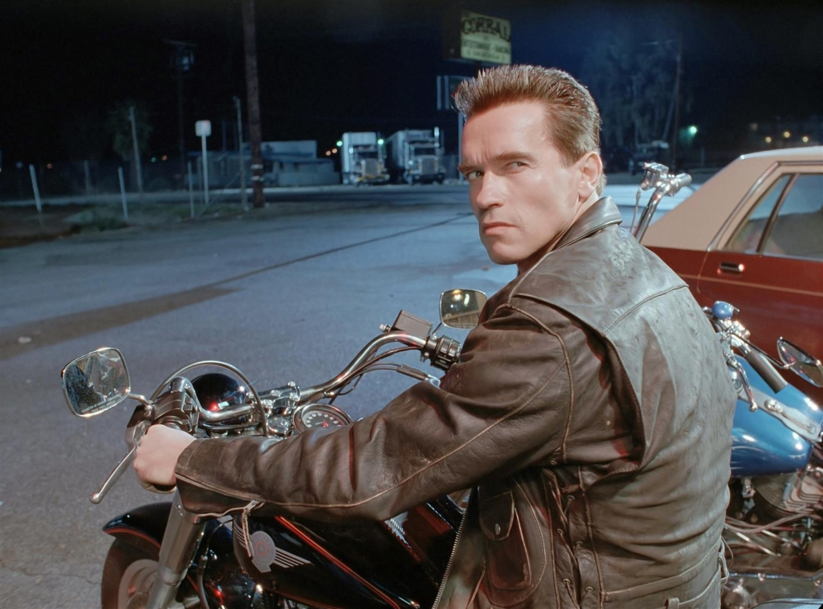 The terminator looks over his shoulder while sitting on a motorcycle