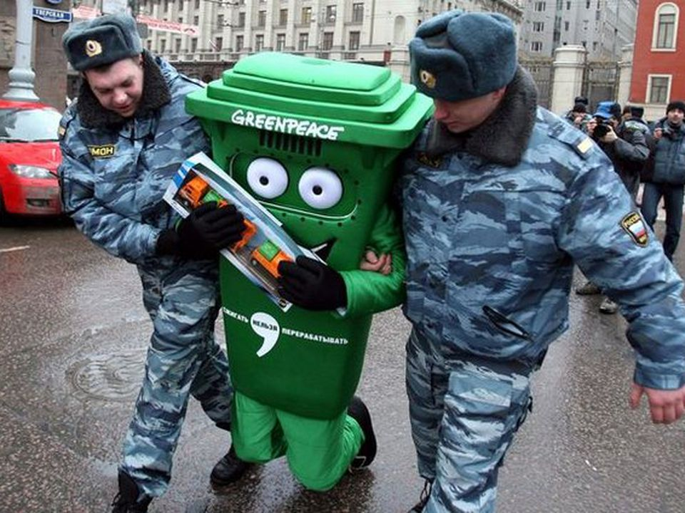 A person dressed in a green trashcan is dragged by police.