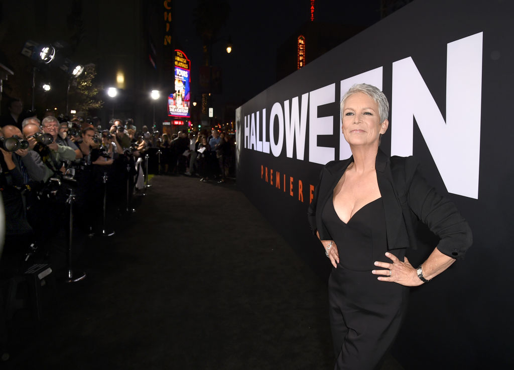 Jamie Lee Curtis poses in front of a giant Halloween poster.