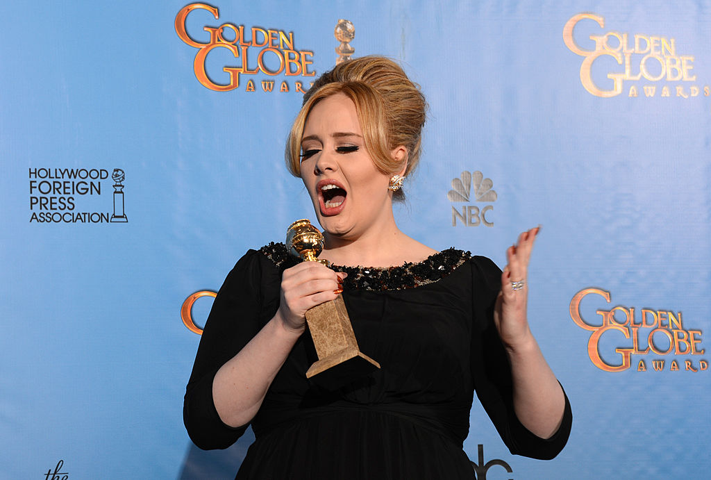 Adele singing into the statuette like it's a microphone,