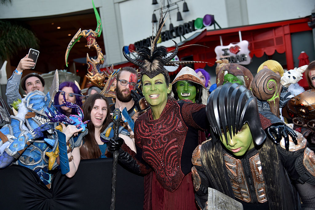 Dressed in cosplay, Jamie and her son pose with a crowd for a photo.