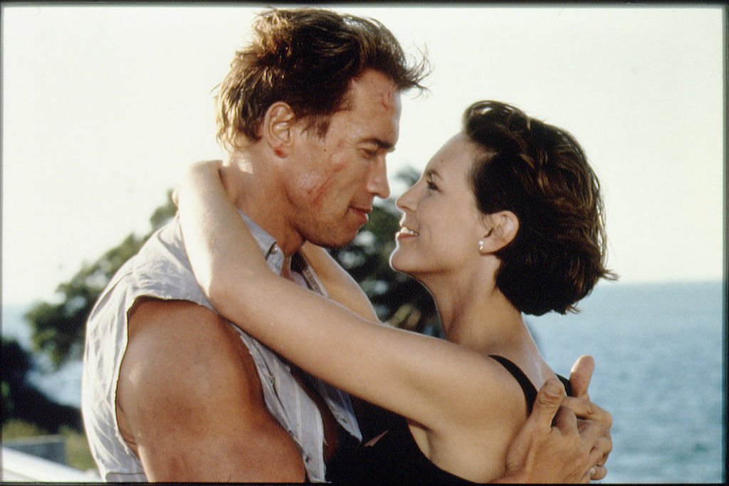 Arnold Schwarzeneggar and Jamie Lee Curtis embrace while filming True Lies.