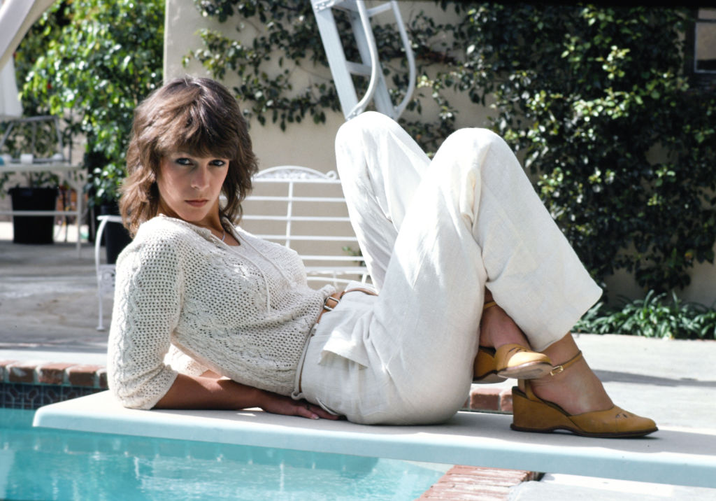 A youthful Jamie Lee Curtis poses near a pool.