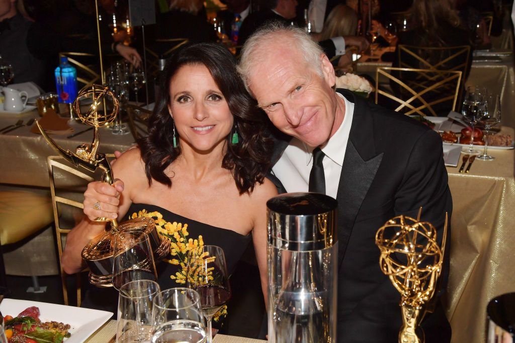 Julia Louis-Dreyfus holding her emmy awards with husband brad hall