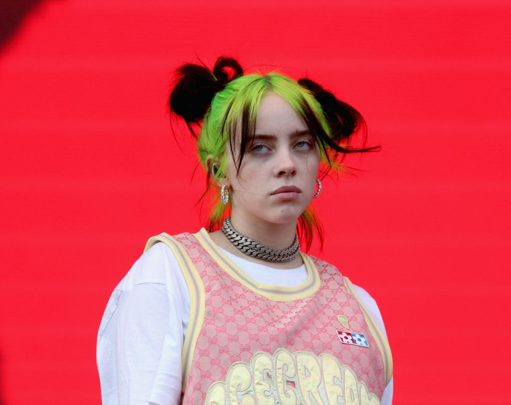 billie eilish with green and black hair in front of a red backdrop