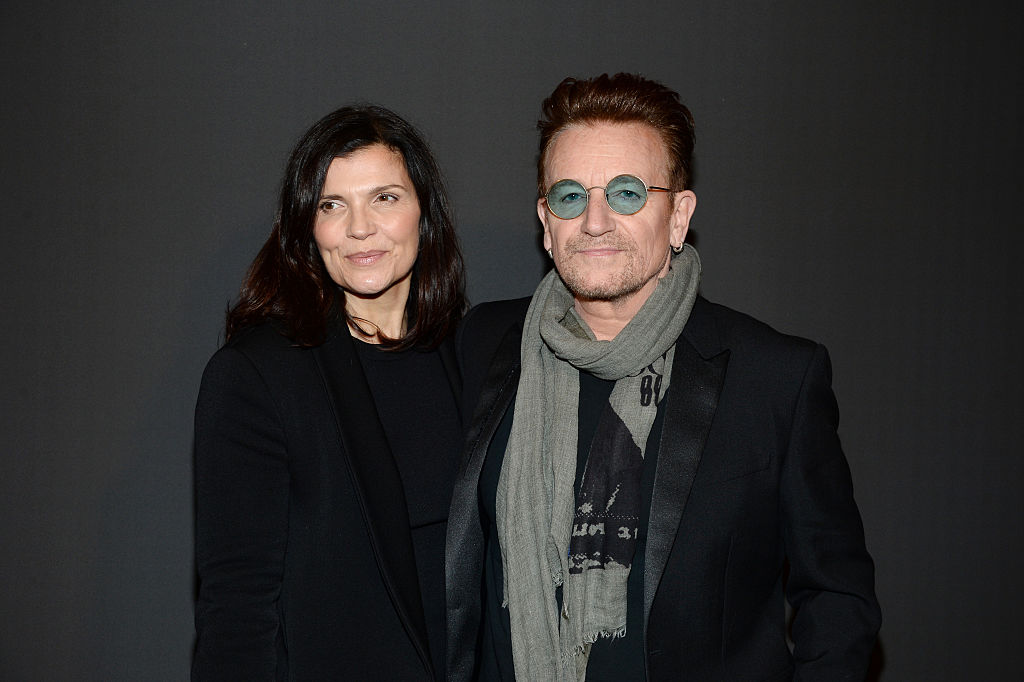 bono wearing green tinted sunglasses and a scarf with his wife alison hewson