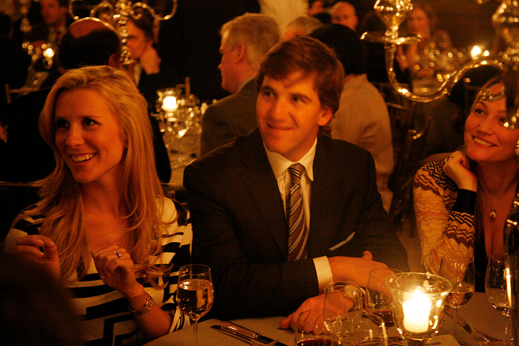 eli manning and wife abby mcgrew sitting at a dinner table