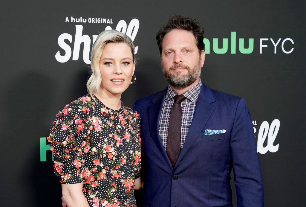 elizabeth banks in a floral dress with husband max handelman in a blue suit at a red carpet event