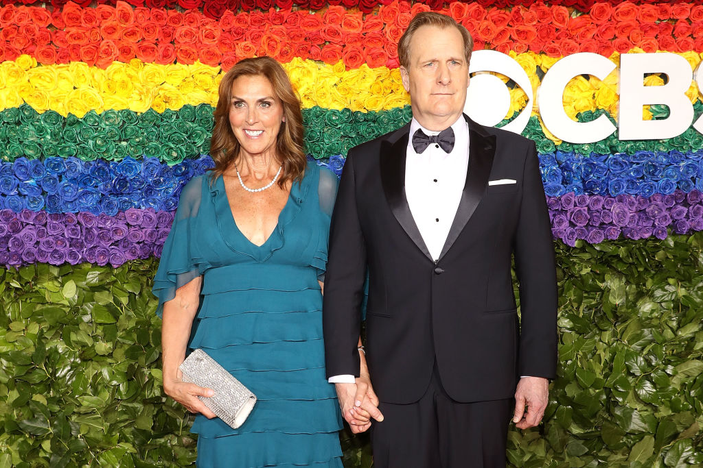 jeff daniels wearing a tuxedo with his wife kathleen treado in a teal dress against a wall of rainbow flowers