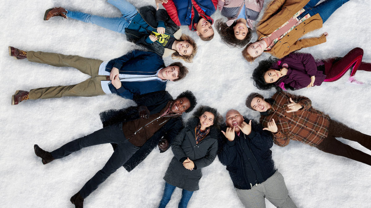 the cast of let it snow laying in a circle in the snow