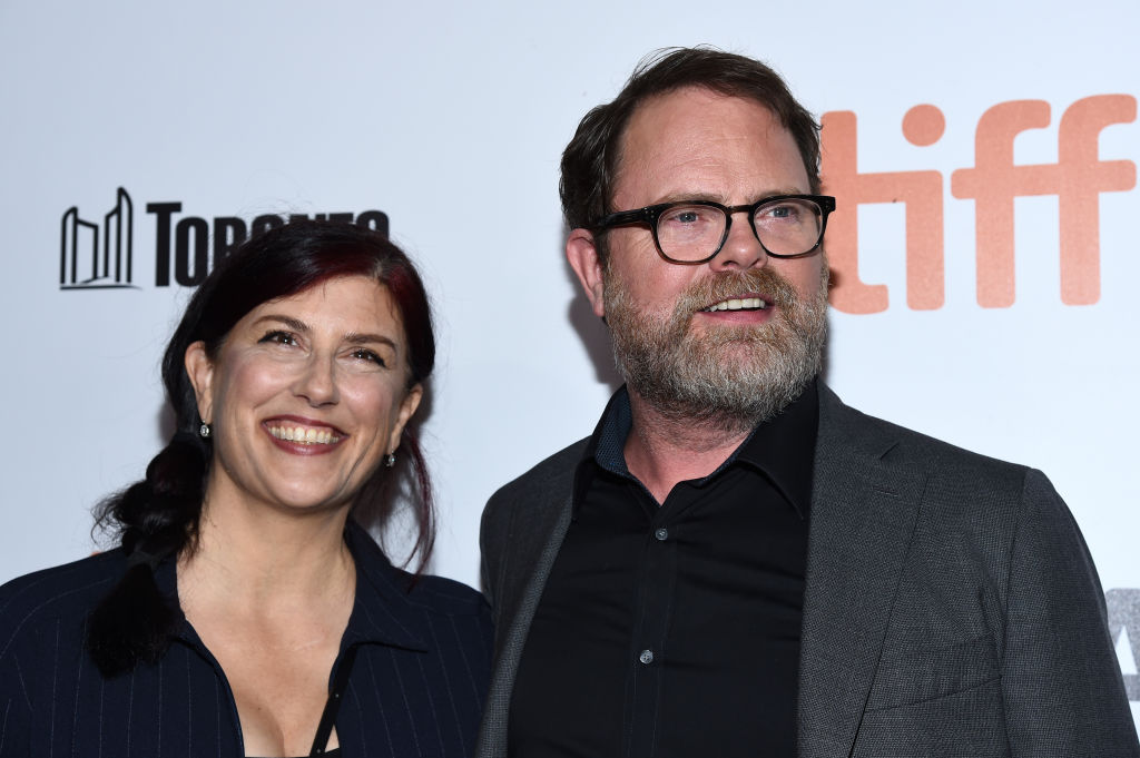 rainn wilson with a beard and glasses and wife holiday reinhorn on a red carpet