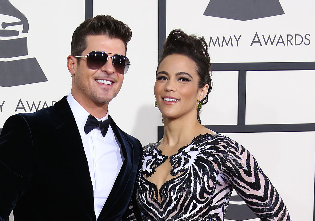 robin thicke in a tuxedo and sunglasses with paula patton in a sequin zebra dress