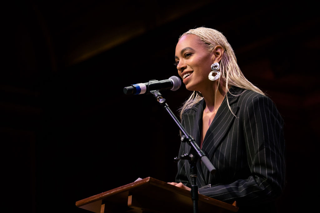 solange knowles speaking into a microphone at a podium