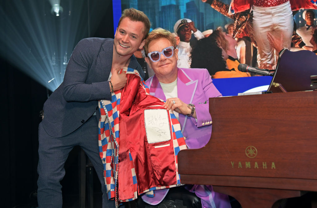 taron egerton and elton john holding a jacket by a piano