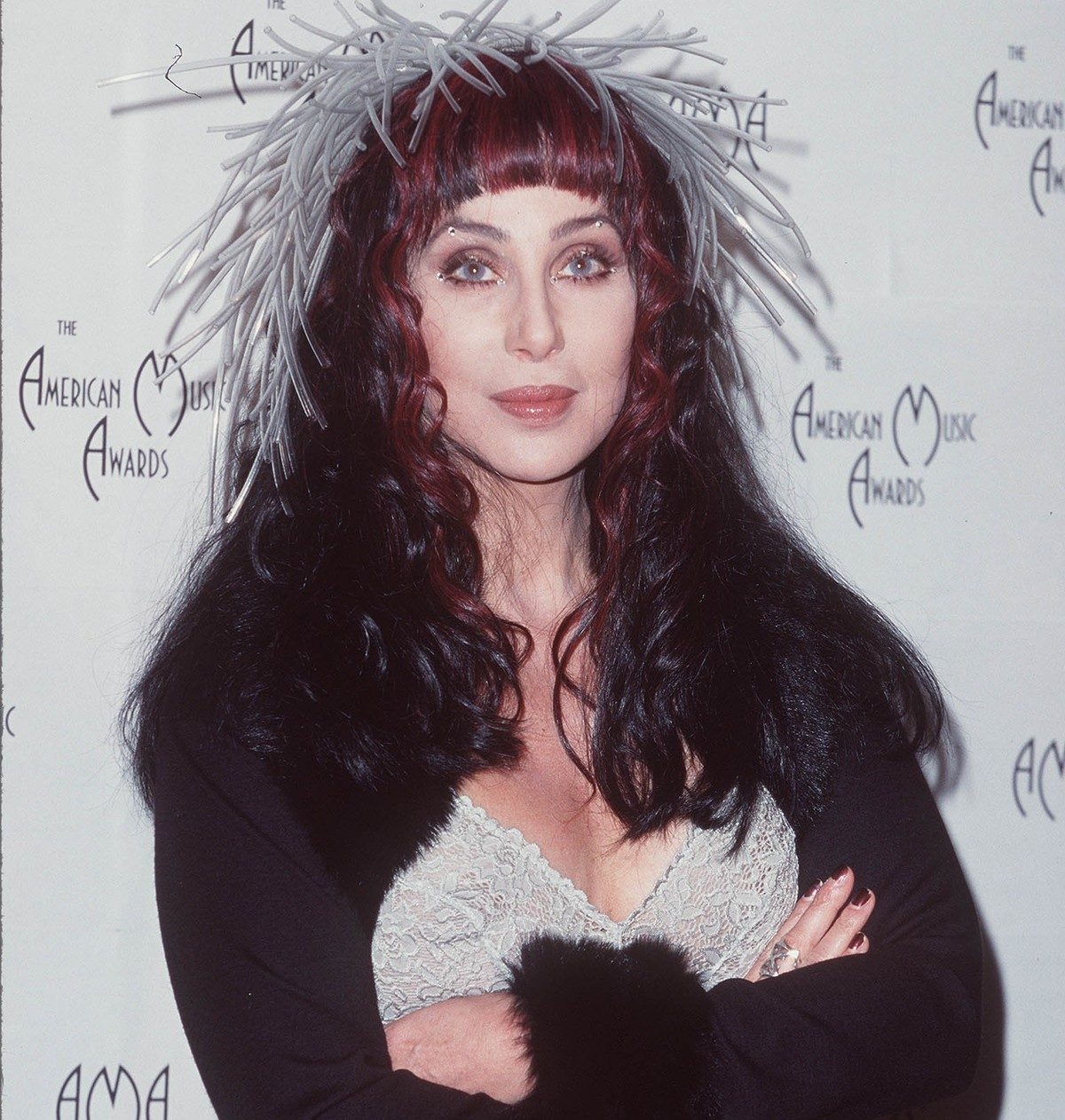 Cher wears an odd headpiece and has her arms crossed and a straight face.