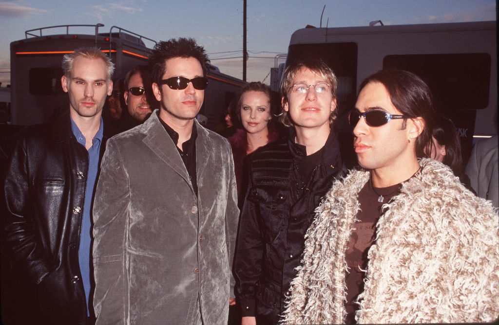 Rockband Third Eye Blind poses in front of actress Charlize Theron.