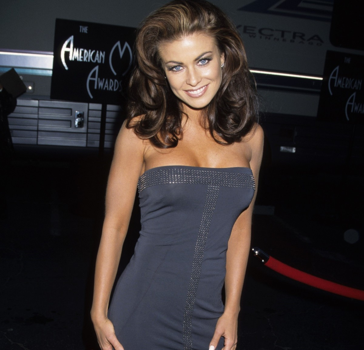 Carmen Electra smiles while wearing a form-fitting gray dress.