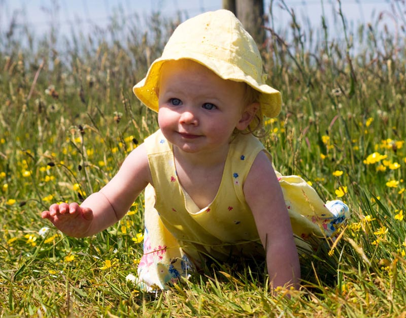 A baby girl crawls in the grass.