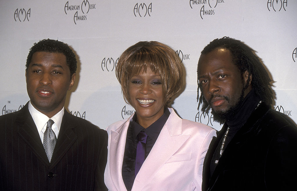 Babyface, Whitney Houston, and Wyclef Jean pose together for a photo.