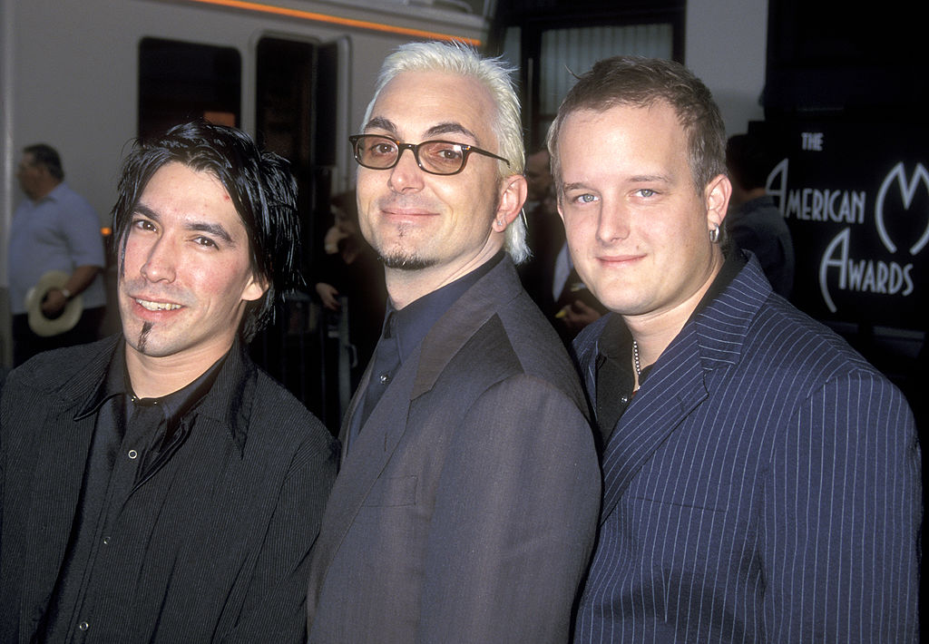 The three musicians in the rockband Everclear pose next to one another.