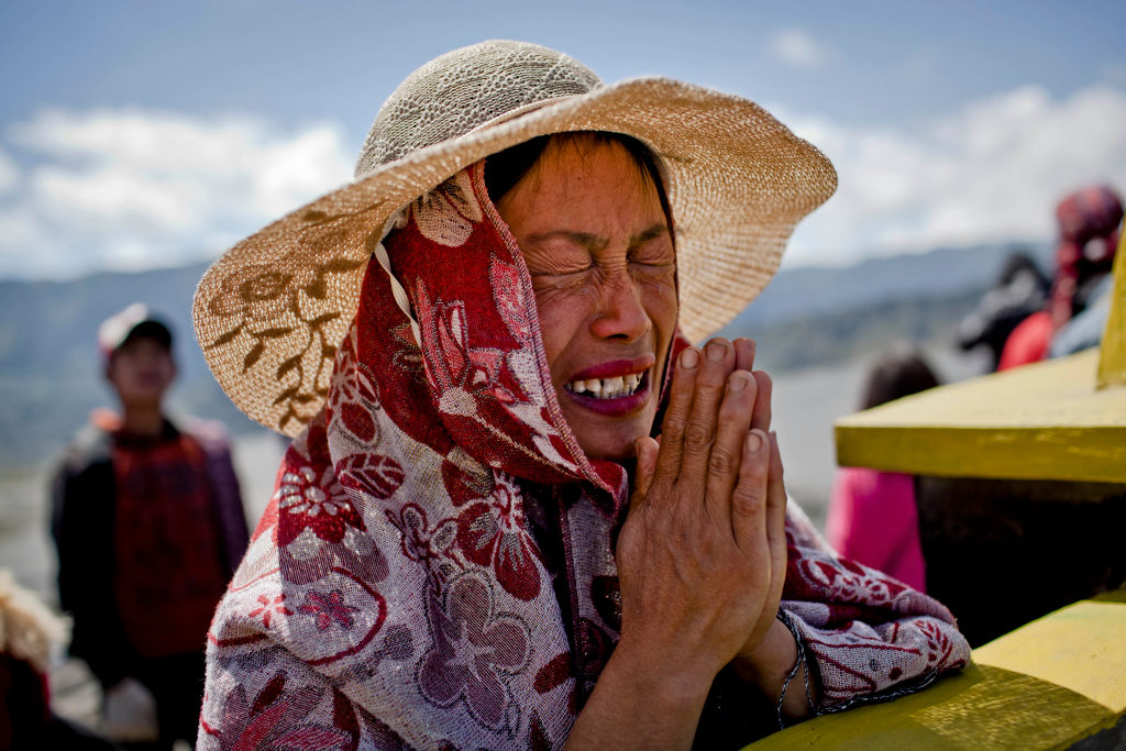 A woman squeezes her eyes together while she prays.