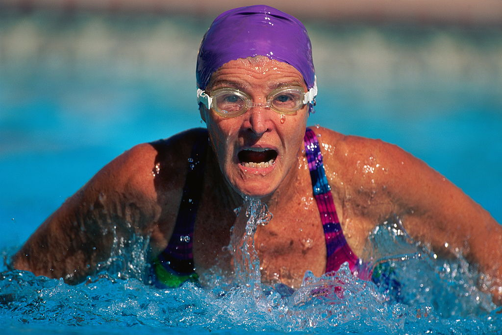 A female swimmer emerges from the water for air.