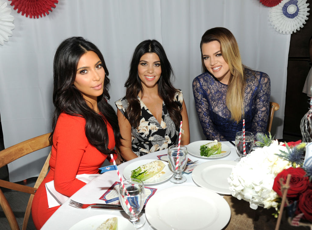 The Kardashian sisters pose at an event.
