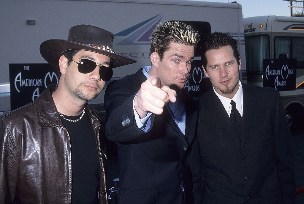 The member of Sugar Ray pose next to one another and the lead singer points to the camera.