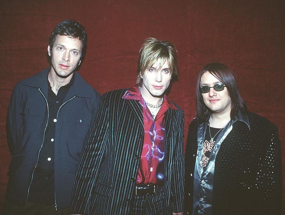 Members of the band Goo Goo Dolls pose with slight smirks.