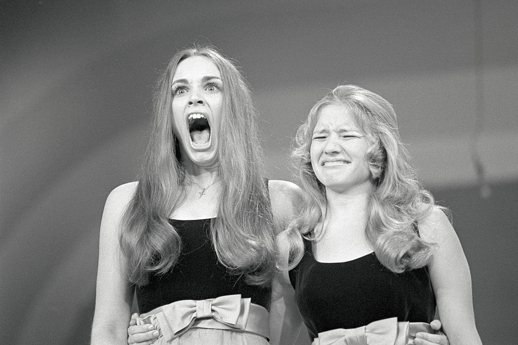 One young woman screams while standing next to another who scrunches up her face.